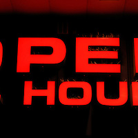 A bright red sign announces that a store is open 24 hours a day.