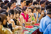 17 APRIL 2013 - BANGKOK, THAILAND:  People lined up six deep at the counter of a gold shop in Bangkok to buy gold Wednesday morning. Thais flocked to gold shops in Bangkoks's Chinatown this morning to buy gold. Wednesday was the first day most gold shops were open after a five day holiday weekend. Shops were closed Friday through Tuesday, when global gold prices dropped by more than 13% based on jitters that Cyprus might liquidate its gold stocks. The Thailand Futures Exchange (TFEX) suspended trading of all gold and silver futures for a short time Tuesday morning because of instability in the market. Gold is now about 22 percent below the record peak of $1,920.30 an ounce set in September 2011. Thais buy gold as both jewelry and an investment, a hedge against inflation and financial failures. Bangkok's Chinatown district is the center of Thailand's gold trade.   PHOTO BY JACK KURTZ