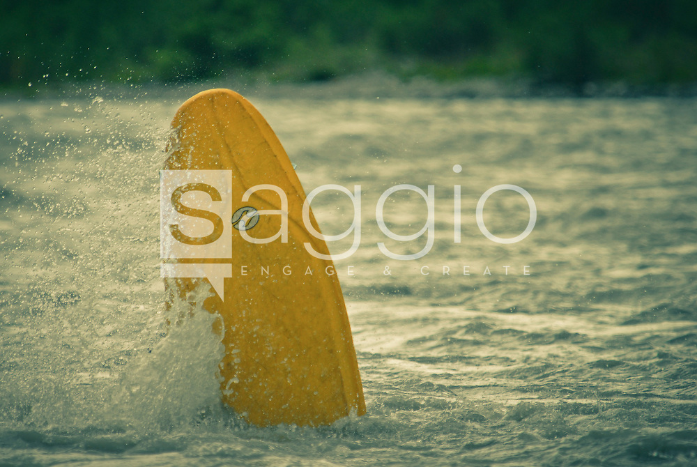 Kayakers play in the waves of the Nenana River near Healy, Alaska.