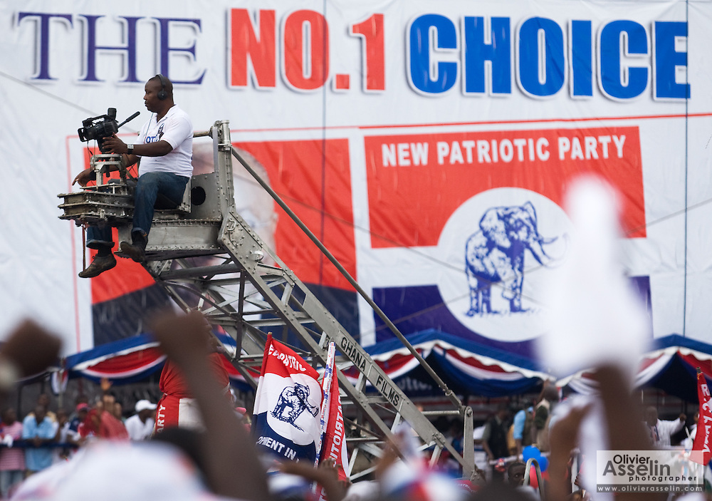 A television cameraman sits on a crane above the crowd during a political rally organized by the New Patriotic Party (NPP), the party currently holding power, in Ghana's capital Accra on Friday December 5, 2008. Ghanaians are voting in a presidential election on December 7 as incumbent John Agyekum Kufuor is to step down after ruling for 2 consecutive 4-year terms.