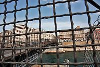 Taranto, maggio 2013.l ponte Girevole (o ponte di San Francesco di Paola) di Taranto è la struttura che collega l'isola del Borgo Antico con la penisola del Borgo Nuovo. Inaugurato il 22 maggio 1887 dall'Ammiraglio Ferdinando Acton, il ponte sovrasta un canale navigabile lungo 400 metri e largo 73 metri che unisce il Mar Grande al Mar Piccolo. È l'unico ponte mobile esistente in Italia..Il ponte misura attualmente 89,9 metri di lunghezza e 9,3 metri di larghezza. Costruito dall'Impresa Industriale Italiana di Napoli su progetto dell'Ing. Giuseppe Messina che ne diresse i lavori di costruzione, era originariamente costituito da un grande arco a sesto ribassato in legno e metallo, diviso in due braccia che giravano indipendentemente l'una dall'altra attorno ad un perno verticale posto su uno spallone. Il funzionamento avveniva grazie a turbine idrauliche alimentate da un grande serbatoio posto sul Castello Aragonese adiacente, capace di 600 metri cubici di acqua che in caduta azionavano le due braccia del ponte..La struttura venne successivamente rimodernata negli anni 1957-1958, introducendo un funzionamento di tipo elettrico, ma mantenendo di fatto inalterati i principi ingegneristici della allora costituenda Direzione del Genio Militare per la Marina. Il progetto fu realizzato dalla Società Nazionale Officine di Savigliano, per tutto quello che riguardava gli organi meccanici ed i comandi elettrici. Il nuovo ponte fu inaugurato dal Presidente della Repubblica Giovanni Gronchi il 10 marzo 1958, e venne intitolato a San Francesco di Paola, protettore delle genti di mare..Il ponte Girevole è sottoposto periodicamente ad accurati interventi di manutenzione, sia degli organi meccanici che dell'intera struttura metallica. Ciascun semiponte che costituisce di fatto la sua struttura, ruota intorno ad un perno centrale ancorato tramite tirafondi alla banchina in cemento, muovendosi sopra una cremagliera mediante un pignone sempre in presa azionato da un motore elettrico. Il
