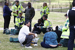 © Licensed to London News Pictures. 27/06/2020. London, UK. Evacuated residents receive medical help on the grass outside their tower block. Fire brigade and other emergency services are dealinh with a fire in a block of flats in Kennington, south London. Photo credit: Peter Macdiarmid/LNP