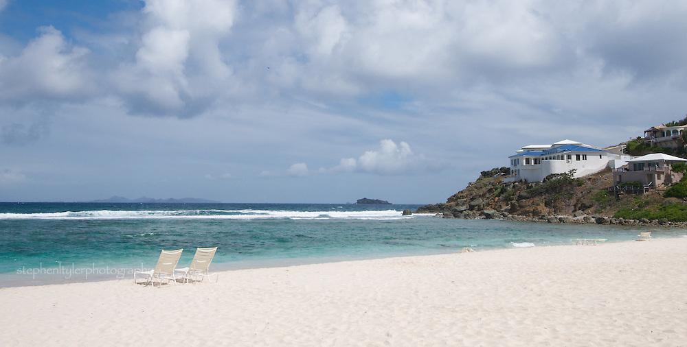 pair of lounge chairs on white beach of Saint Martin