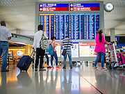 14 AUGUST 2013 - HONG KONG: Passengers check flight status boards at Hong Kong International Airport. Dozens of flights were delayed at one of the busiest airports in Asia and Hong Kong raised their alert to level 8, the highest, and closed schools and many businesses because of Severe Typhoon Utor. The storm passed within 260 kilometers of Hong Kong before making landfall in mainland China. Severe Typhoon Utor (known in the Philippines as Typhoon Labuyo) is an active tropical cyclone located over the South China Sea. The eleventh named storm and second typhoon of the 2013 typhoon season, Utor formed from a tropical depression on August 8. The depression was upgraded to Tropical Storm Utor the following day, and to typhoon intensity just a few hours afterwards. The Philippines, which bore the brunt of the storm, reported 1 dead in a mudslide and 23 fishermen missing at sea.   PHOTO BY JACK KURTZ