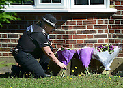 © Licensed to London News Pictures. 07/09/2012. Claygate, UK A police officer lays some flowers on the family's front lawn. The family home of Saad al-Hilli in Claygate, near Esher. Three members ofof the family have been shot dead in the French Alps. Photo credit : Stephen Simpson/LNP