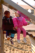 Friends age 4 talking on school yard playground.  St Paul  Minnesota USA