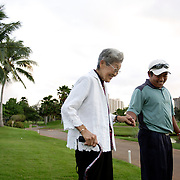 HONOLULU, HAWAII, November 8, 2007: Tadd Fujikawa, a sixteen-year-old professional golfer, walks his great grandmother back to her golf cart after practice in Honolulu Country Club in Honolulu, Hawaii. (Photographs by Todd Bigelow/Aurora)