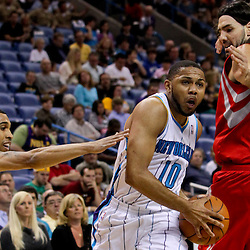 April 19, 2012; New Orleans, LA, USA; New Orleans Hornets shooting guard Eric Gordon (10) drives between Houston Rockets power forward Luis Scola (4) and shooting guard Courtney Lee (5) during the first quarter at the New Orleans Arena. The Hornets defeated the Rockets 105-99.  Mandatory Credit: Derick E. Hingle-US PRESSWIRE