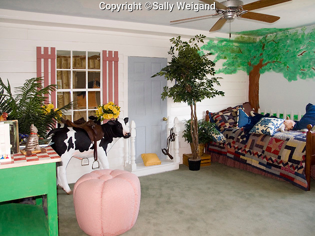 child's bedroom decorated with picket fence; painted flowers; cow; false window & door; appealing
