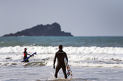 Surfers at Fistral Beach in Newquay, Cornwall.