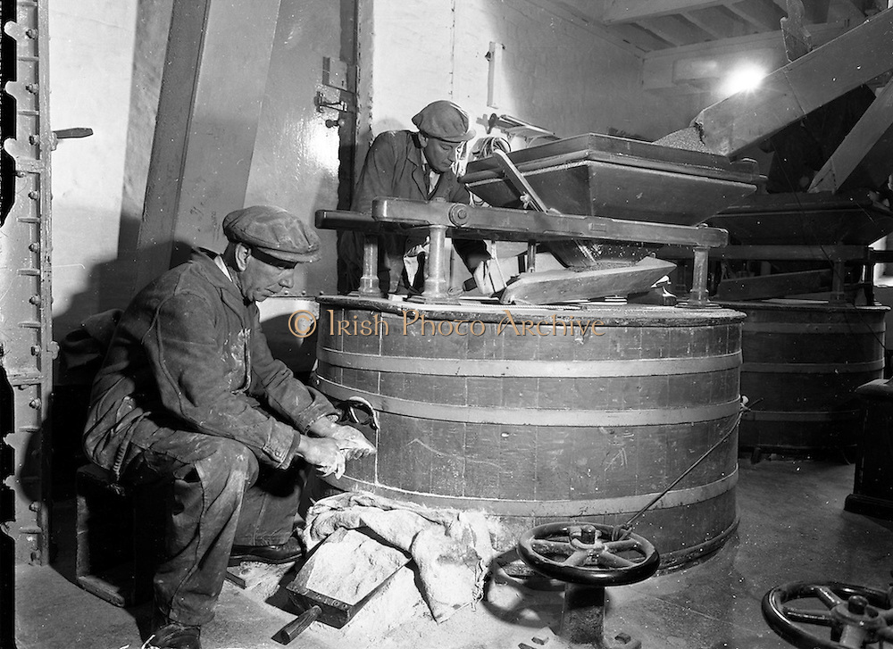 16/12/1959<br /> 12/16/1959<br /> 16 December 1959<br /> <br /> Miller George Anderson and John Maher grinding Barley in a 120 year old Millstone grinder