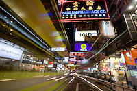 Buses go by both sides of the camera amidst the hustle and bustle of the Causeway Bay area in Hong Kong, China.