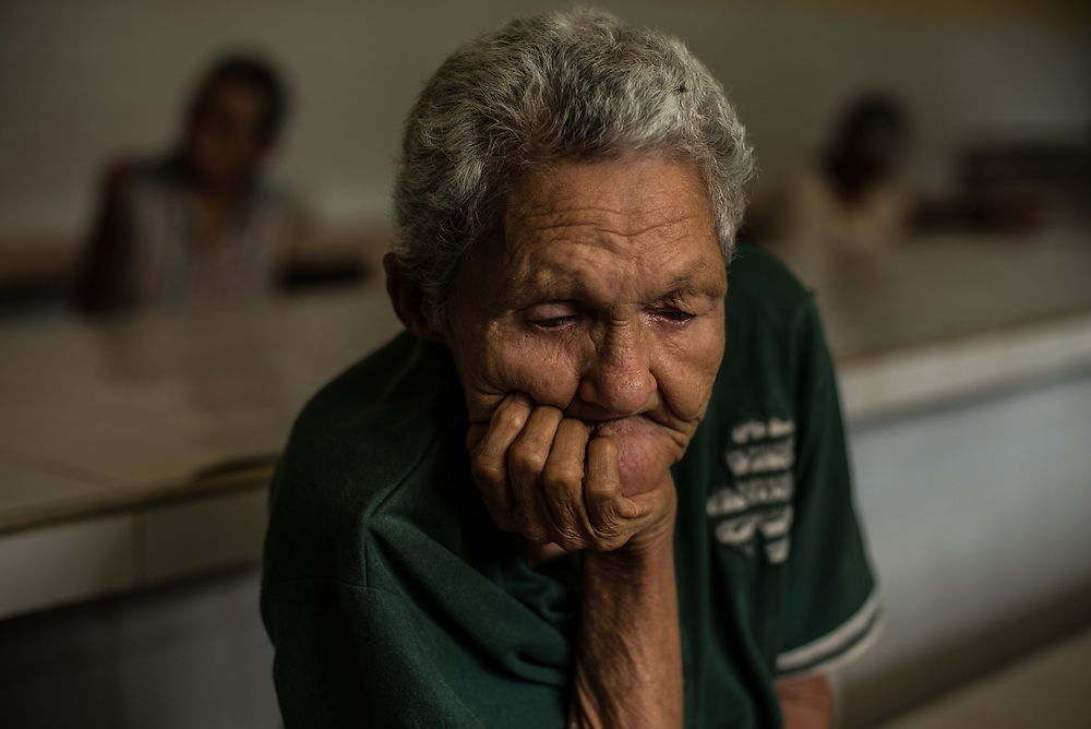 BARQUISIMETO, VENEZUELA - JULY 28, 2016:  Paranoid schizophrenic<br /> Carmen Lucena cries quietly while waiting for dinner to be served. She has bilateral cataracts and cannot see. She needs help from the nurses and other patients to walk to different areas of the hospital.  The economic crisis that has left Venezuela with little hard currency has also severely affected its public health system, crippling hospitals like El Pampero Psychiatric Hospital by leaving it without the resources it needs to take care of patients living there, the majority of whom have been abandoned by their families and rely completely on the state to meet their basic needs, and who could live much more fulfilling lives if they had the medicines that they need.  PHOTO: Meridith Kohut for The New York Times