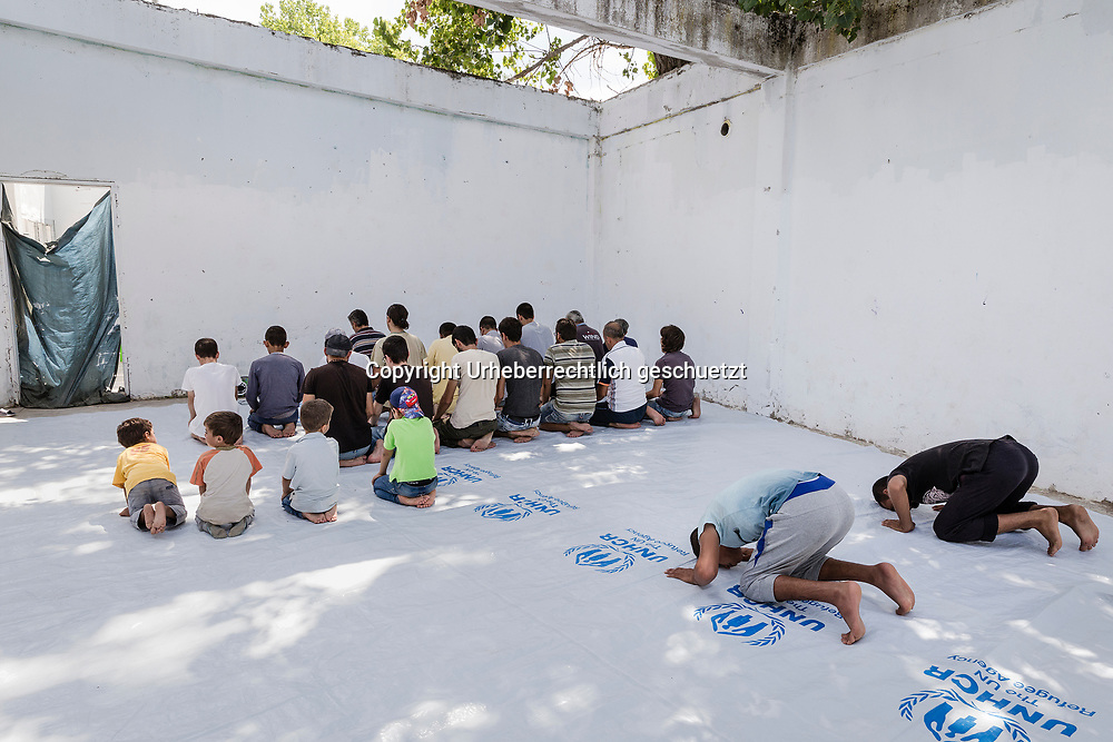 Greece, Lagkadikia, Fridays pray, several men, youngsters and boys come together to pray on Friday early afternoon together in a dilapidated building. The floor is covered with wide plastic sheets from the UNCHR. Mohammad Alkamell, (2 R, with white T-shirt ) and Judi, ( 2 L, first row) are between these Syrian refugees praying.