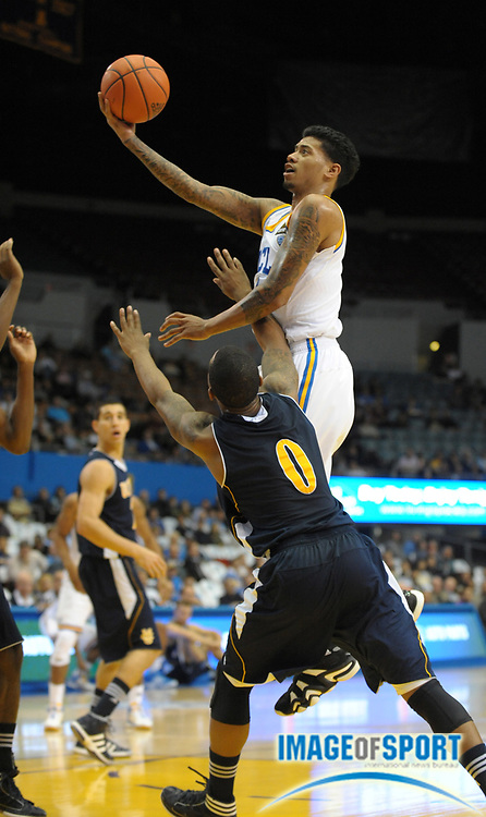 Dec 20, 2011; Los Angeles, CA, USA; UCLA Bruins guard Tyler Lamb (1) is defended by UC Irvine Anteaters guard Derick Flowers (0) at the Los Angeles Memorial Sports Arena. UCLA defeated UC Irvine 89-60.