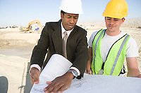 Surveyor and construction worker studying blueprint