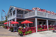 The Dock House restaurant on the Beaufort waterfront on the Crystal Coast of North Carolina, with cheerful red umbrellas and outdoor dining.