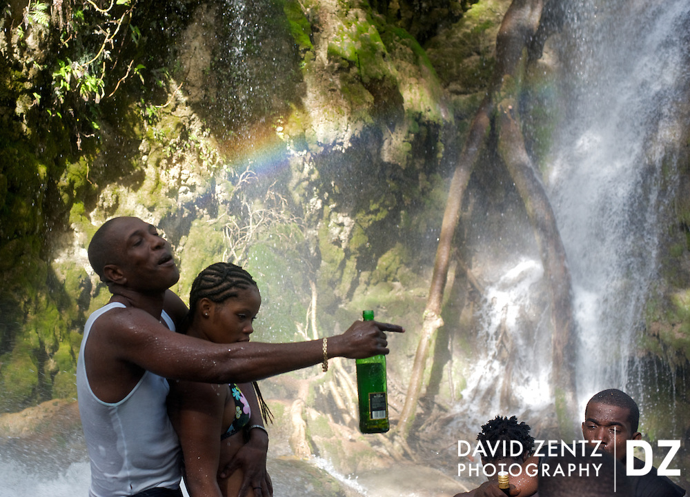 A young couple stands with others in the cleansing waters of Saut D'eau, in Haiti, during the annual voodoo pilgrimage there in July