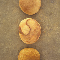 Three smooth brown pebbles lined up on brown stone surface