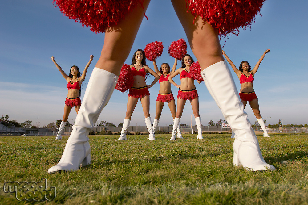 Cheerleader in white knee high boots low section with cheerleaders behind