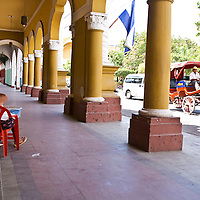 A woman sits by Granada's main square, selling food to passer bys. A horsedrawn cart passes her on the street. Granada is Nicaragua's most famous city. founded in 1524 it is one of best examples of Spanish colonial architecture in the Americas.it has a varied history including its almost total destruction by filibuster William Walker in a childlike tantrum. Today it is a popular tourist town though retains a strong sense of its own identity.