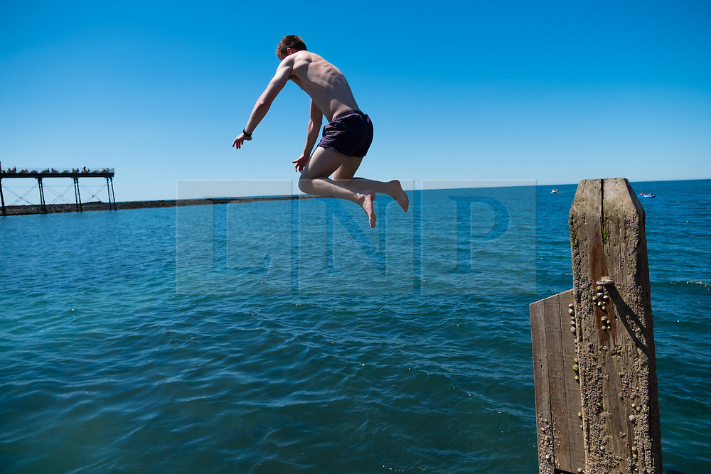 © Licenced to London News Pictures<br /> 28 June 2018 . Aberystwyth Wales UK<br /> <br /> UK Weather:  On another scorchingly hot day at the seaside in Aberystwyth, people flock to the beach and sea to top up their tans and cool down  a little in the clear shallow  waters of Cardigan Bay<br /> The UK is in the grips of a mini heatwave, with temperatures reaching over  30º Celsius in many parts of the country<br /> photo credit Keith Morris / LNP