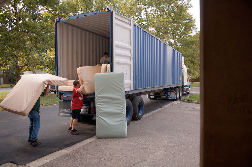 "Members of the moving crew move beds into semi truck.... 8/16/2007..Contact: Sustainability Coordinator Sonia Marcus at 740-593-0026, marcuss@ohio.edu, or Ed Newman, Manager of Campus Recycling & Refuse at 740-593-0231, newmane@ohio.edu..Mattresses Without Borders.Furniture Donation Program Helps Hurricane Victims...The Department of Campus Recycling and Refuse has been busy loading used mattresses. Hundreds of them. But this time, they're not headed to a landfill - they're headed to needy recipients throughout the Caribbean who are storing supplies to get them through the upcoming hurricane season...""Instead of sending the mattresses to a landfill, I'm getting them re-used,? explained Ed Newman, manager of Campus Recycling & Refuse. ?The cost of shipping is the same as the cost of sending them to our own landfill. This way a lot of people will get use out of them.""..Newman has been partnering with the Institutional Recycling Network and Food for the Poor on this innovative re-use project. Mattresses that have outlived their use in our campus residence halls are loaded directly onto shipping containers at the Ridges shop that are then sent out directly to those in need. With the support of Moving Services and custodial staff members, Campus Recycling has shipped three containers of mattresses so far this summer, and is getting ready to load another up today. Two more are scheduled for September. Newman estimates that each container holds between 200 and 215 mattresses...The Housing Office fully supports the initiative. ?I think that none of us wants to see anything wasted,? said Beverly Wyatt, director of the department. ?Part of our mission at this university is service to others. This is one small way that we can serve the world at large.?"