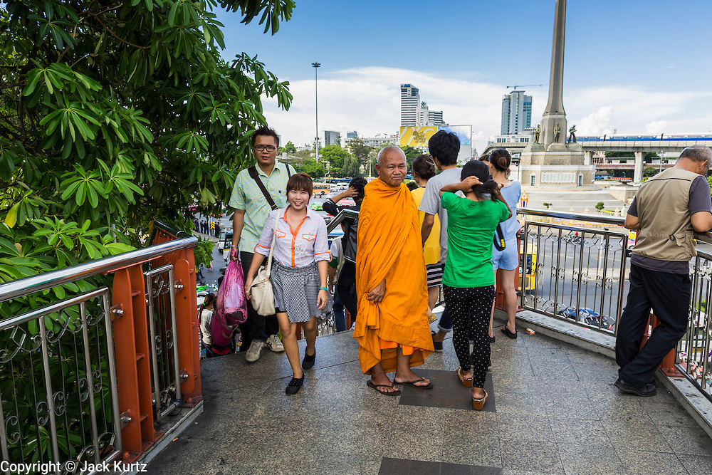 31 MAY 2014 - BANGKOK, THAILAND:  A Buddhist monk stands in the skywalk at Victory Monument in Bangkok. Victory Monument has been the principal gathering spot for anti-coup protests since a military coup deposed the elected government on May 22. Victory Monument was quiet Saturday with hundreds of police and military stationed around it to dissuade protestors. Bangkok was mostly quiet Saturday. There were only a few isolated protests against the coup and military government.   PHOTO BY JACK KURTZ