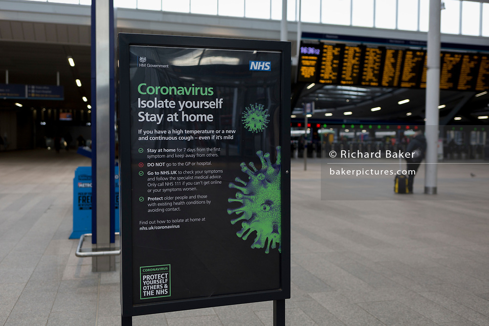 As the UK government announces further Coronavirus-related restrictions to its citizens, with the immediate closure of pubs, cafes, gyms and cinemas, and the worldwide number of deaths reaching 10,000 with 240,000 cases, 953 of those in London alone, a lone commuter waits for their train near an NHS information notice about staying at home, on the concourse of London Bridge Station, on 20th March 2020, in London, England.