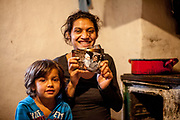 Klara (22) holding a photograph from exactly one year ago where she is pictured with her son Krstian, on the left side 4 years old daughter Maria. in their home at the Roma settlement in Ostrovany.