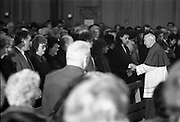 Funeral Of Eamon Andrews.   (R67)..1987..10.11.1987..11.10.1987..10th November 1987..Today saw the funeral of the broadcaster,Eamon Andrews. The funeral mass was held in St Anne's Church, Portmarnock, Co Dublin with the removal to Balgriffin Cemetery, Co Dublin...Image shows one of the co-celebrant priests offering condolences to the family of the late Eamon Andrews.