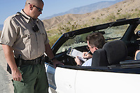 Policeman with driver signing speeding ticket