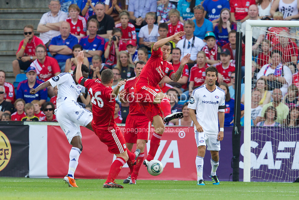 OSLO, NORWAY - Monday, August 1, 2011: Liverpool's Charlie Adam and Daniel Agger tackle Valerenga's Fegor Ogude for a penalty kick during a preseason friendly match at the Ulleval Stadion. (Photo by Vegard Grott/Propaganda)