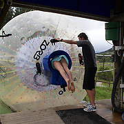 Participants enter a Zorb Globe preparing for  a ride down the hill. The sport of Zorb globe riding was invented in New Zealand and globes are designed, manufactured and tested there, The Zorb globe is an 11 foot high inflatable transparent sphere which you can ride inside. Two feet of air protect you from the ground enabling you to globe ride down hills at high.  Agrodome, Western Rd. Ngongotahaha.  Rotorua, New Zealand,, 11th December 2010 Photo Tim Clayton..