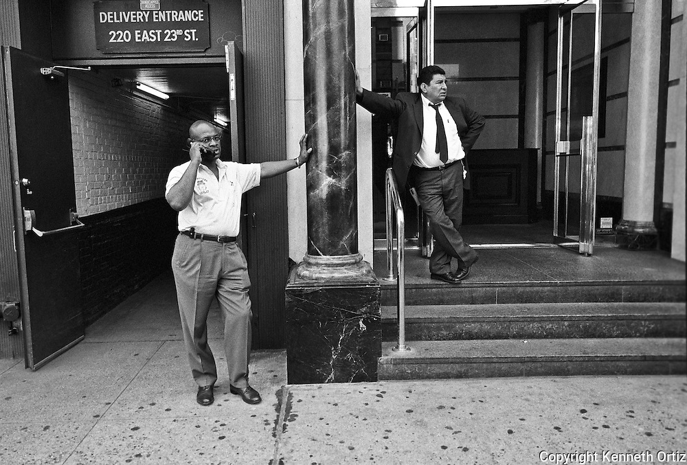 Two guys leaning against a column in front of 220 East 23rd street.