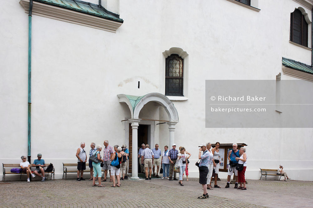 Elderly tourists exit and gather out a church in the city of Cortina d'Ampezzo, Veneto, Italy.