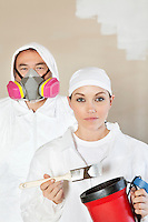 Portrait of female worker holding paint tools with male worker standing behind