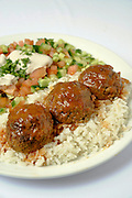 A serving of Meatballs on rice with salad and tahini
