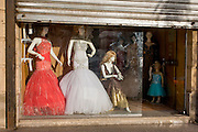 Mannequins in the window of a clothing business displaying womens' dresses for special occasions in modern Luxor, Nile Valley, Egypt.