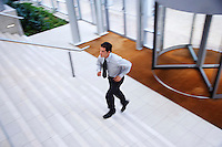 Businessman running up stairs in office lobby