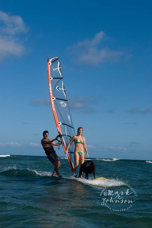Couple & pet dog windsurfing together, Oahu, Hawaii
