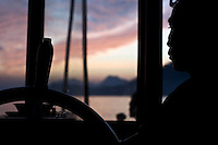 A boat captain steers his vessel down the Mekong River in Laos as it travels towards Luang Prabang.