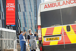 © Licensed to London News Pictures . 21/04/2020. Manchester, UK. An advert telling people to STAY HOME is displayed on the face of the Axis Tower building as hospital staff wave goodbye to one of the first patients to be discharged from the hospital , as an ambulance takes him home . The National Health Service has built a 648 bed field hospital for the treatment of Covid-19 patients , at the historical railway station terminus which now forms the main hall of the Manchester Central Convention Centre . The facility is treating patients from across the North West of England , providing them with general medical care and oxygen therapy after discharge from Intensive Care Units . Photo credit : Joel Goodman/LNP