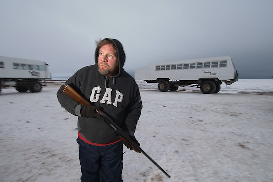 Kevin Burke stands guard watching for polar bears as others break down the camp for the move to Cape Churchill.