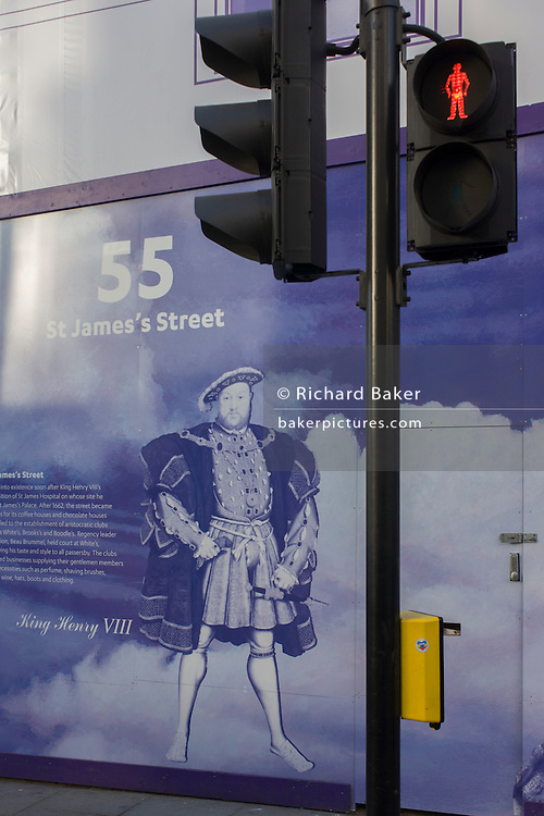King Henry VIII (8th) on a construction hoarding alongside a red standing pedestrian light in central London.