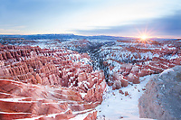 Sunrise illuminates the orange spires and snow of Bryce Canyon National Park.