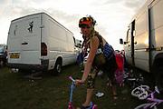 Photographer Molly Macindoe on a children's scooter, Boomtown, Matterley Estate, Alresford Road, near Winchester, Hampshire, UK, August, 2010