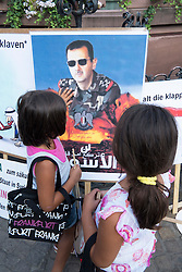Young girls look at portrait of Assad at Syrian Pro-Assad demonstrators protest against against civil war in Syria and against outside involvement by the US and UN in historic Römerberg square in central Frankfurt Germany.