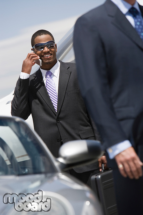 Mid-adult businessman using mobile phone outside of car.