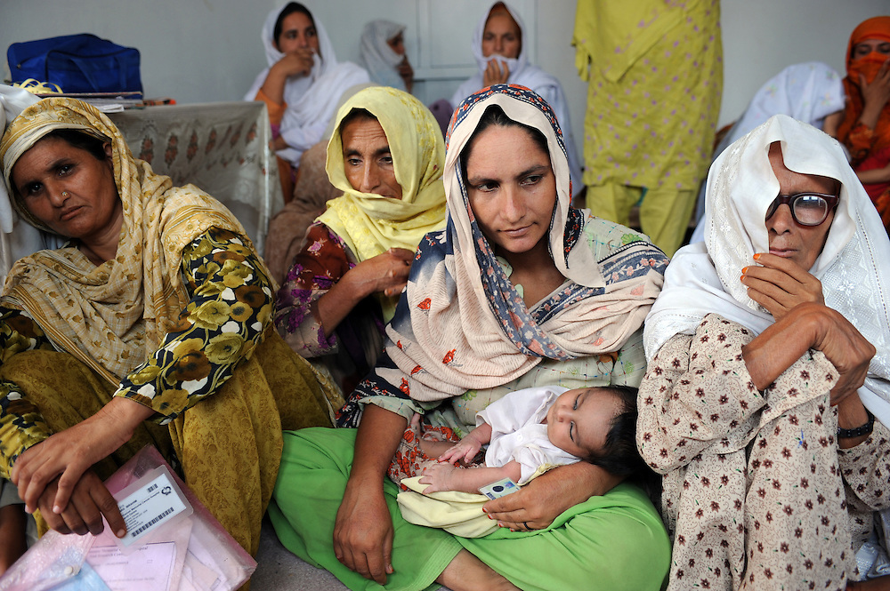 "7/8/2009 Gulmina (centre) from Mandeara, Swat with her new baby Sajit who was nicknamed ""evacuee from Swat boy"". Heavily pregnant and with her husband and four children, she escaped the heavy bombing and shelling by walking 3km before getting a lift. Jalala, Pakistan"